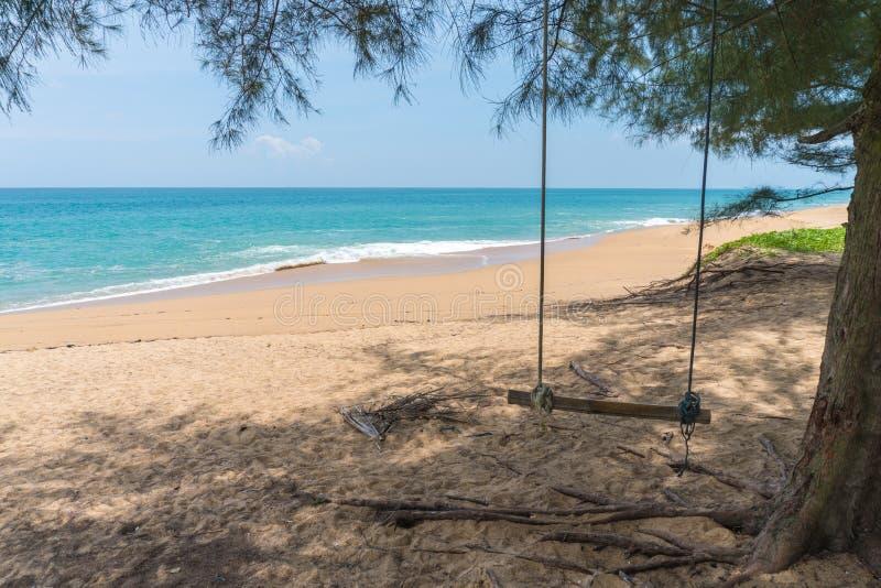 Ταλάντευση με το μπλε ουρανό δέντρων και το υπόβαθρο σύννεφων, μπλε θάλασσα και άσπρη παραλία άμμου στην παραλία της Mai Khao σε  στοκ εικόνα με δικαίωμα ελεύθερης χρήσης