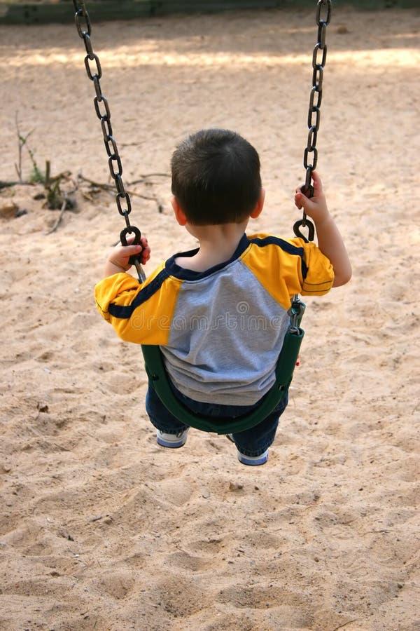 ταλάντευση πάρκων αγοριών στοκ εικόνες