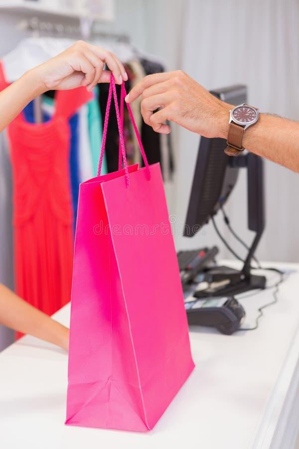 Ταμίας που δίνει στον πελάτη μια ρόδινη τσάντα αγορών στοκ φωτογραφίες με δικαίωμα ελεύθερης χρήσης