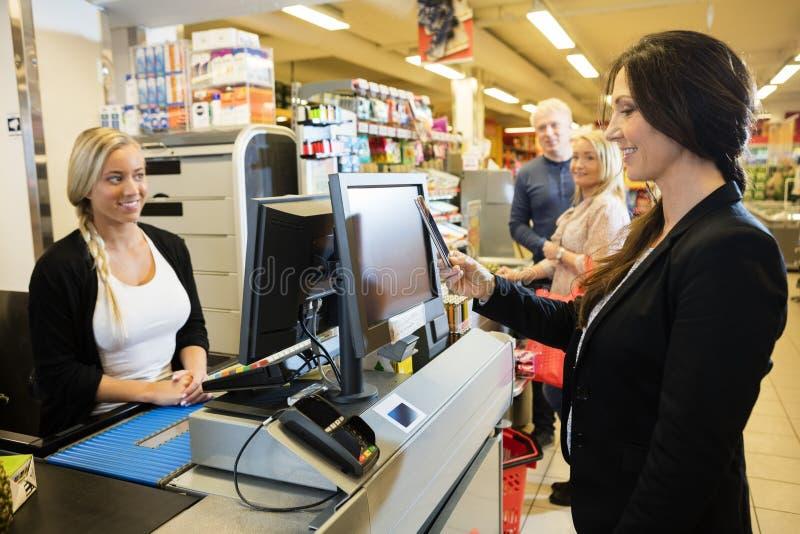 Ταμίας που εξετάζει το θηλυκό πελάτη που κάνει την πληρωμή NFC στοκ εικόνα