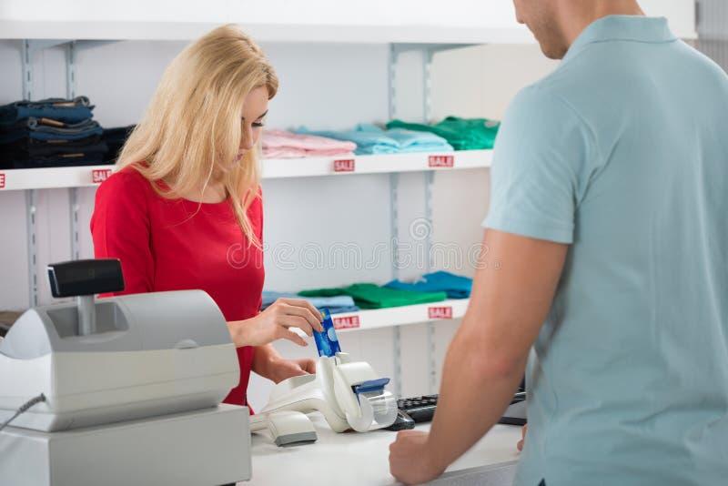 Ταμίας που χρησιμοποιεί την πιστωτική κάρτα στεμένος με τον πελάτη στοκ εικόνα με δικαίωμα ελεύθερης χρήσης