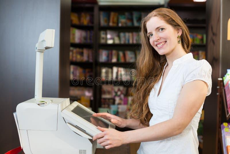 Ταμίας στον κατάλογο μετρητών στο βιβλιοπωλείο στοκ εικόνες