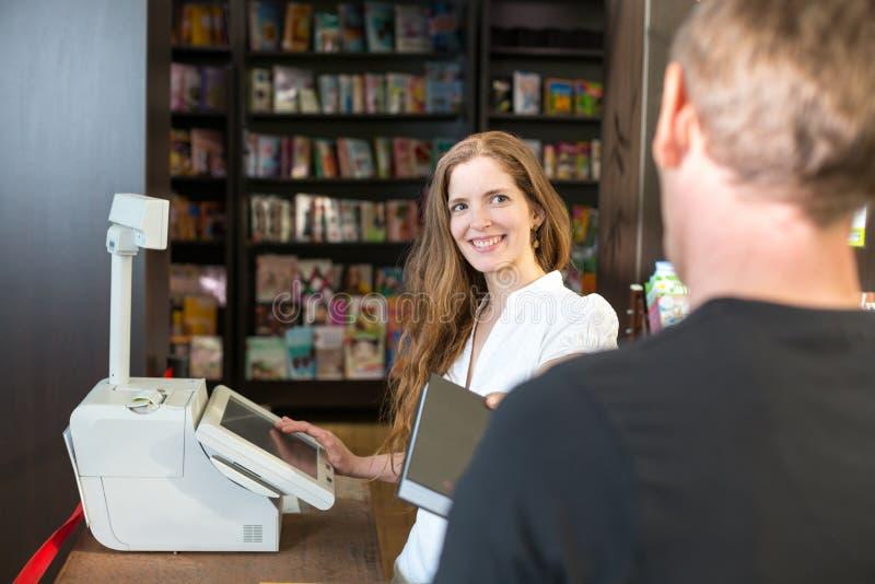 Ταμίας στο βιβλιοπωλείο που εξυπηρετεί έναν πελάτη ή έναν πελάτη στοκ εικόνες