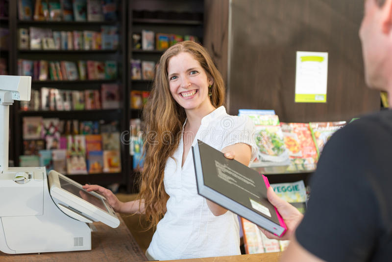 Ταμίας στο βιβλιοπωλείο που εξυπηρετεί έναν πελάτη ή έναν πελάτη στοκ φωτογραφίες