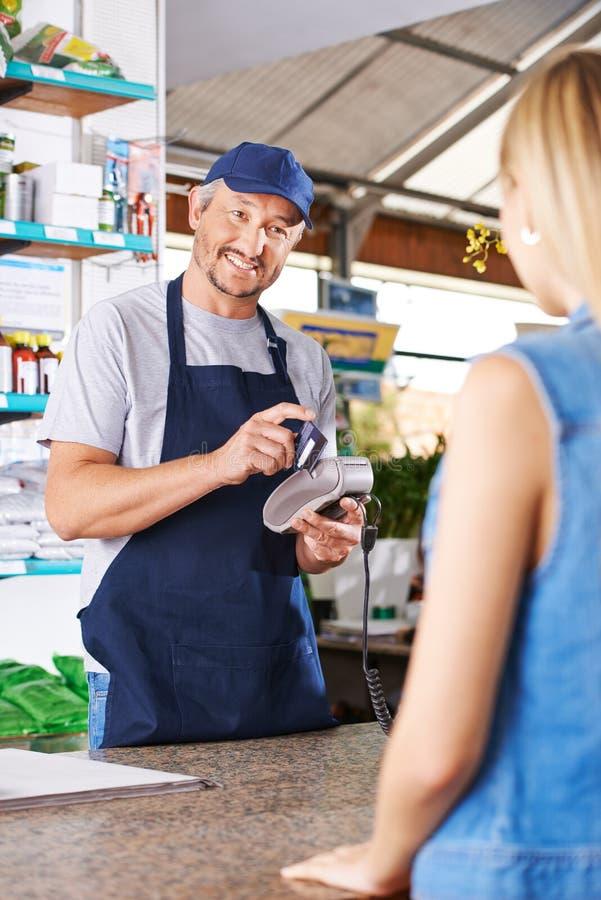 Ταμίας στο μαγαζί λιανικής πώλησης με την πιστωτική κάρτα στοκ εικόνα με δικαίωμα ελεύθερης χρήσης