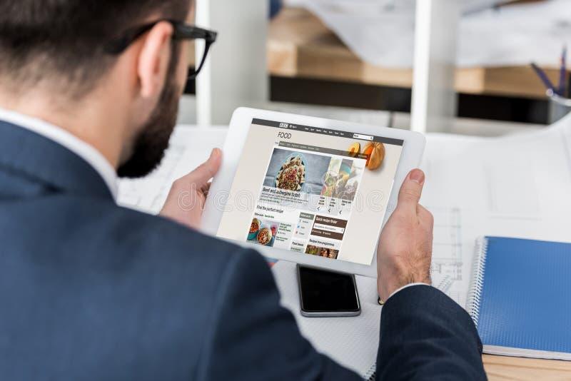 ταμπλέτα εκμετάλλευσης επιχειρηματιών με τη φορτωμένη σελίδα τροφίμων BBC στοκ εικόνες