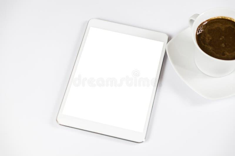 Ταμπλέτα υπολογιστών με την άσπρη κενή οθόνη δίπλα στον καφέ Η ταμπλέτα είναι στον άσπρο πίνακα κορυφαία όψη Κινηματογράφηση σε π στοκ φωτογραφία με δικαίωμα ελεύθερης χρήσης