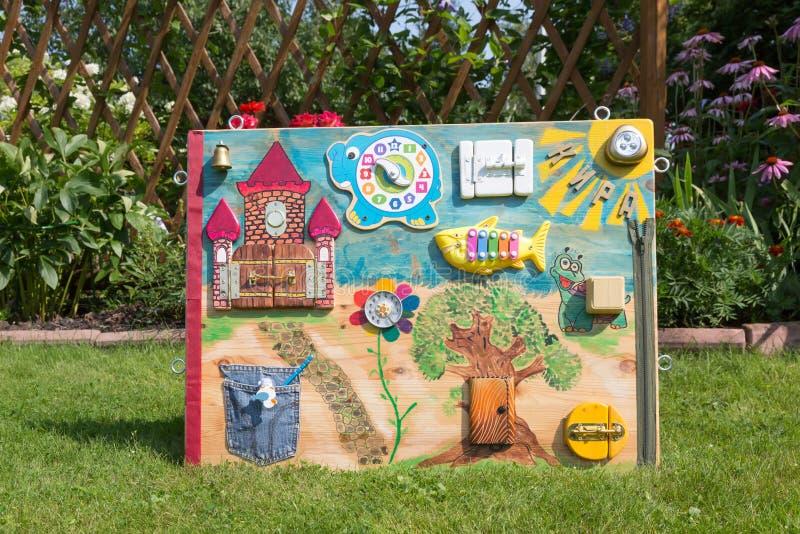 ταμπλό παιχνιδιών του σπιτικού μωρού montessori στον πράσινο χορτοτάπητα υ στοκ φωτογραφία