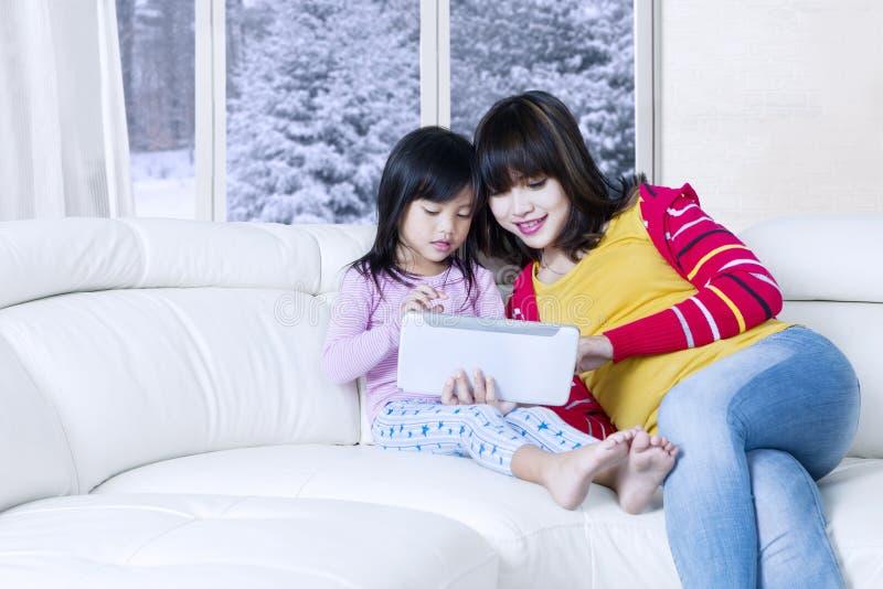 Ταμπλέτα λαβής γυναικών και κοριτσιών στον καναπέ στοκ φωτογραφία