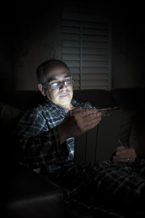 Ταμπλέτα ανάγνωσης ατόμων τη νύχτα στοκ εικόνα με δικαίωμα ελεύθερης χρήσης