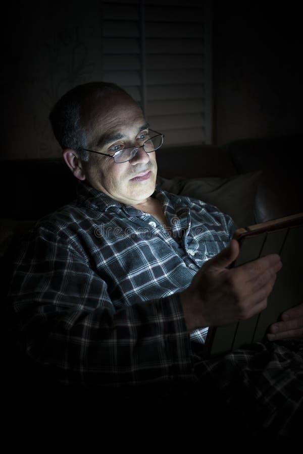 Ταμπλέτα ανάγνωσης ατόμων τη νύχτα στοκ φωτογραφίες