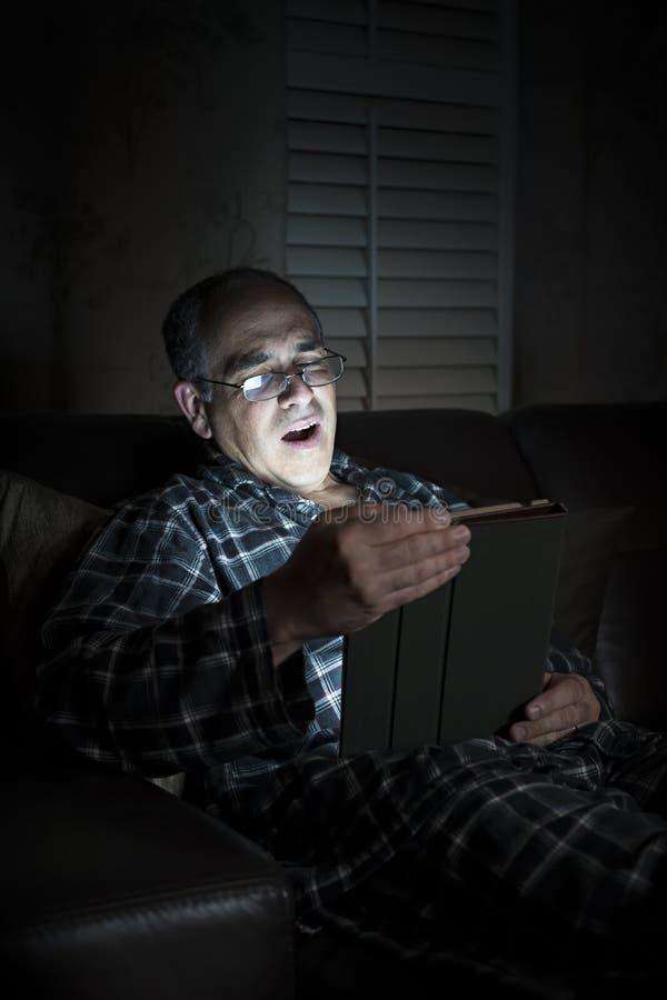 Ταμπλέτα ανάγνωσης ατόμων χασμουρητού τη νύχτα στοκ φωτογραφία με δικαίωμα ελεύθερης χρήσης