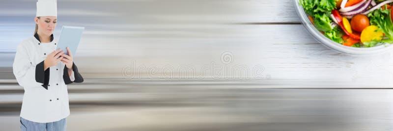 Ταμπλέτα εκμετάλλευσης αρχιμαγείρων με τη σαλάτα και θολωμένο το κίνηση υπόβαθρο στοκ εικόνες με δικαίωμα ελεύθερης χρήσης