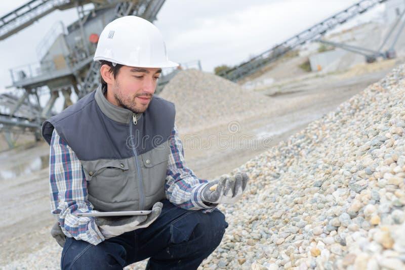 Ταμπλέτα εκμετάλλευσης ατόμων που εξετάζει τις πέτρες σωρών στο λατομείο στοκ εικόνα με δικαίωμα ελεύθερης χρήσης