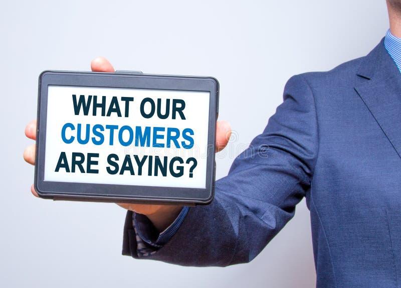 Ταμπλέτα εκμετάλλευσης χεριών επιχειρηματιών με αυτό που οι πελάτες μας είναι Sayi στοκ εικόνες