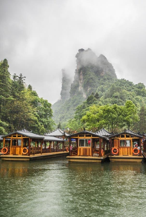 Ταξίδι βαρκών λιμνών Baofeng σε μια βροχερή ημέρα με τα σύννεφα και την υδρονέφωση σε Wulingyuan, πάρκο εθνικών δρυμός Zhangjiaji στοκ εικόνα