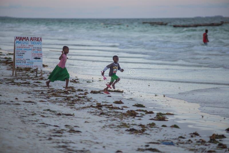 Ταξίδι γύρω από την Τανζανία Δύο από τα παιδιά που τρέχουν κατά μήκος της ακτής στοκ εικόνες