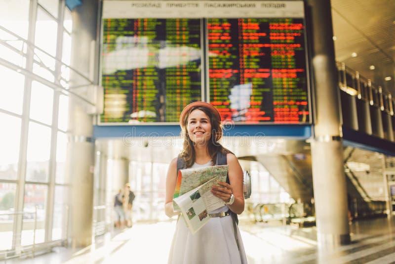 Ταξίδι και μεταφορά θέματος Όμορφη νέα καυκάσια γυναίκα στο φόρεμα και σακίδιο πλάτης που στέκεται μέσα στο τερματικό σταθμών τρέ στοκ φωτογραφία με δικαίωμα ελεύθερης χρήσης