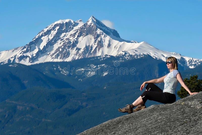 Ταξίδι Καναδάς Γυναίκα στον απότομο βράχο βουνών ενάντια καλυμμένη στη χιόνι αιχμή στοκ φωτογραφία με δικαίωμα ελεύθερης χρήσης