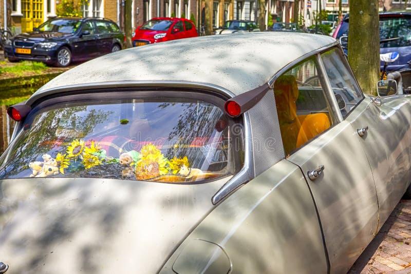 Ταξίδι μέσω της Ευρώπης Ντεμοντέ αναδρομικό αυτοκίνητο με τα λουλούδια στοκ φωτογραφίες