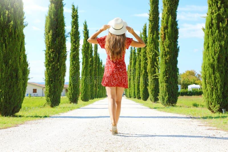 Ταξίδι στην Τοσκάνη Νεαρή γυναίκα περπατάει σε όμορφο και ειδυλλιακό τοπίο μιας λωρίδας κυπαρίσσας στην επαρχία Τοσκάνη στην στοκ φωτογραφίες