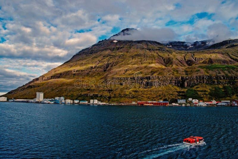 Ταξίδι της Ισλανδίας Επιπλέον σώμα βαρκών στη θάλασσα στο τοπίο βουνών σε Sejdisfjordur, Ισλανδία Παραλία με το βουνό στο νεφελώδ στοκ φωτογραφία με δικαίωμα ελεύθερης χρήσης
