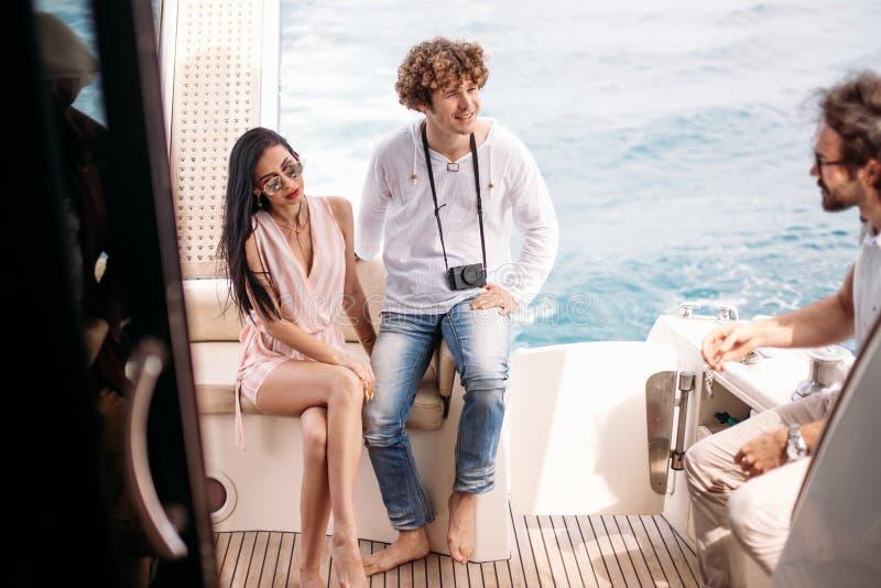 Ταξίδι, seatrip, φιλία και έννοια ανθρώπων - φίλοι που κάθονται στη γέφυρα γιοτ στοκ εικόνες με δικαίωμα ελεύθερης χρήσης