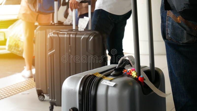 Ταξί αερολιμένων επιβάτης με τις μεγάλες αποσκευές κυλίνδρων που στέκονται στη γραμμή που περιμένει τη σειρά αναμονής ταξί στο χώ στοκ εικόνα
