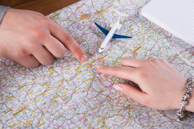 Ταξίδι διακοπών προγραμματισμού ζεύγους στην Ευρώπη, τα χέρια και το υπόβαθρο χαρτών στοκ φωτογραφία