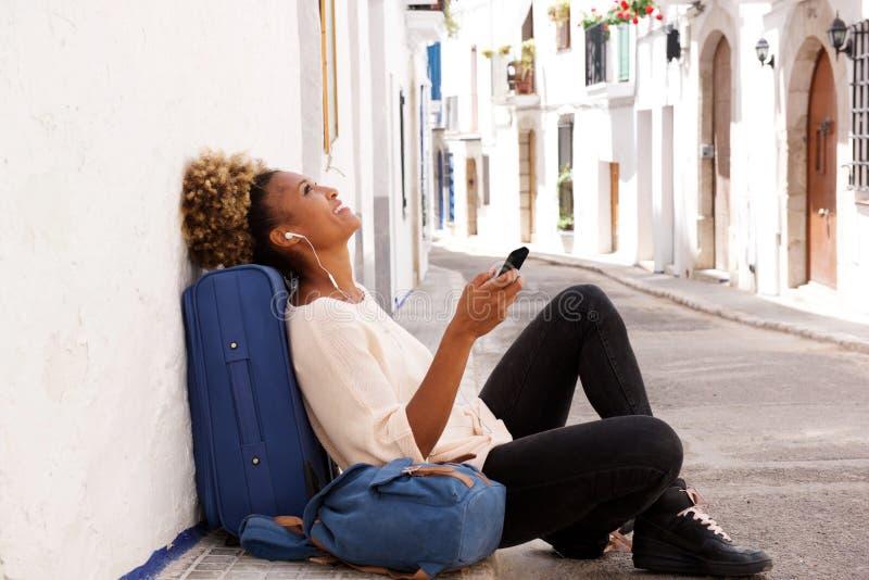 Ταξιδιωτική θηλυκή συνεδρίαση αφροαμερικάνων στο πεζοδρόμιο και μουσική ακούσματος από το έξυπνο τηλέφωνο στοκ φωτογραφία με δικαίωμα ελεύθερης χρήσης