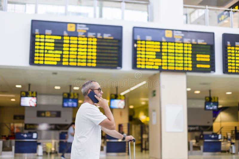 ταξιδιωτικό άτομο που μιλά στο έξυπνο κινητό τηλέφωνό του στον αερολιμένα θολωμένο υπόβαθρο οθονών πληροφοριών ταξίδι και μεταφορ στοκ εικόνες