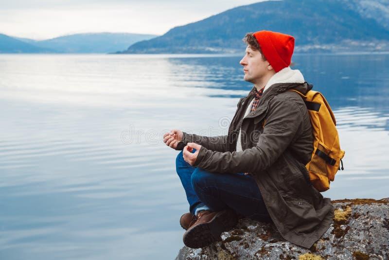 Ταξιδιωτικό άτομο σε μια στοχαστική συνεδρίαση θέσης σε μια δύσκολη ακτή στο υπόβαθρο ενός βουνού και μιας λίμνης Διάστημα για στοκ φωτογραφία με δικαίωμα ελεύθερης χρήσης