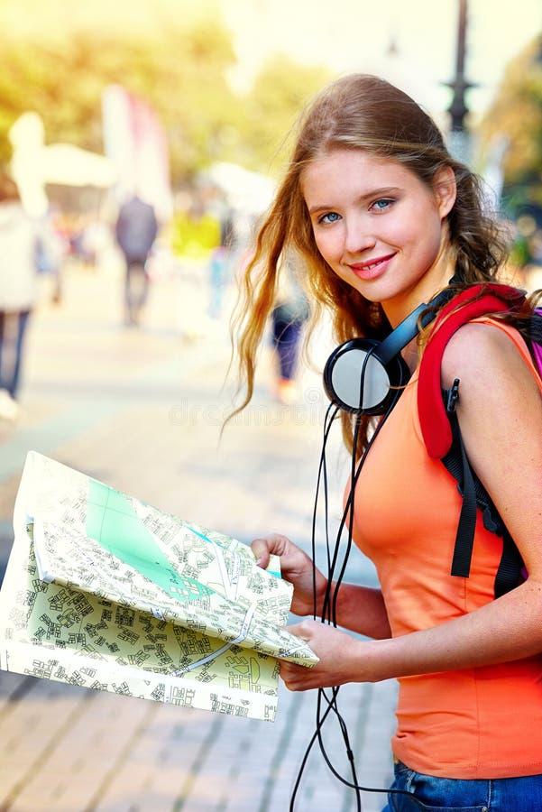 Ταξιδιωτικό κορίτσι με το σακίδιο πλάτης που ψάχνει το χάρτη εγγράφου τουριστών τρόπων στοκ φωτογραφία