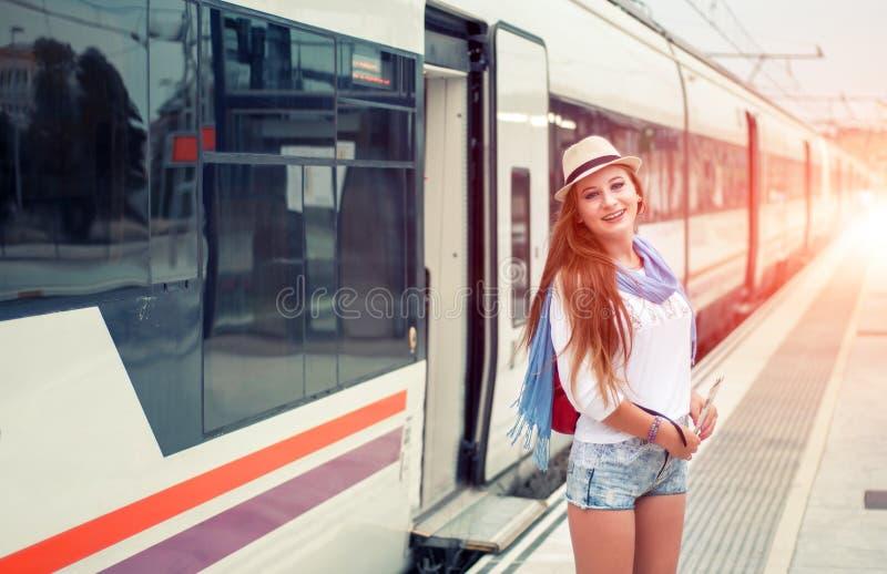Ταξιδιωτικό κορίτσι με το τραίνο περπατήματος χαρτών, καπέλων και σακιδίων πλάτης στο railwa στοκ φωτογραφία με δικαίωμα ελεύθερης χρήσης