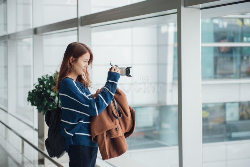 Ταξιδιωτικό νέο ασιατικό κορίτσι με το σακίδιο πλάτης που παίρνει μια φωτογραφία με τη ψηφιακή κάμερα της στοκ εικόνα με δικαίωμα ελεύθερης χρήσης