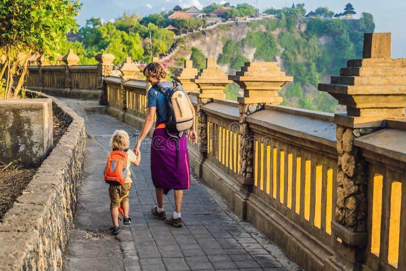 Ταξιδιώτες μπαμπάδων και γιων στο ναό Pura Luhur Uluwatu, Μπαλί, Ινδονησία Καταπληκτικό τοπίο - απότομος βράχος με το μπλε ουρανό στοκ φωτογραφία