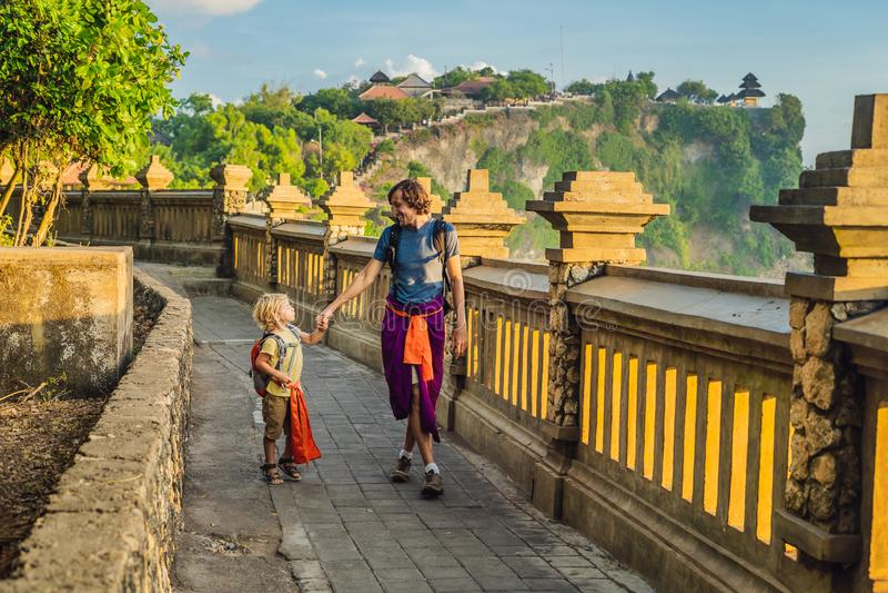 Ταξιδιώτες μπαμπάδων και γιων στο ναό Pura Luhur Uluwatu, Μπαλί, Ινδονησία Καταπληκτικό τοπίο - απότομος βράχος με το μπλε ουρανό στοκ εικόνες