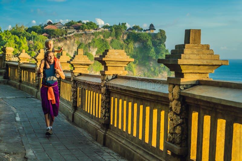 Ταξιδιώτες μπαμπάδων και γιων στο ναό Pura Luhur Uluwatu, Μπαλί, Ινδονησία Καταπληκτικό τοπίο - απότομος βράχος με το μπλε ουρανό στοκ φωτογραφίες