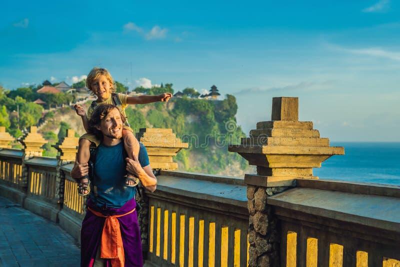 Ταξιδιώτες μπαμπάδων και γιων στο ναό Pura Luhur Uluwatu, Μπαλί, Ινδονησία Καταπληκτικό τοπίο - απότομος βράχος με το μπλε ουρανό στοκ εικόνα με δικαίωμα ελεύθερης χρήσης