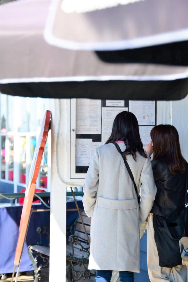 Ταξιδιώτες που εξετάζουν επιλογές μεσημεριανού γεύματος στοκ εικόνα