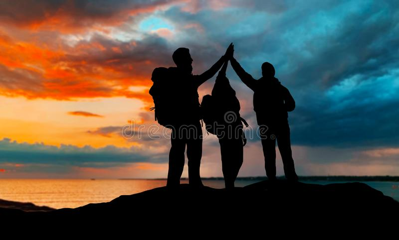 Ταξιδιώτες που κάνουν υψηλά πέντε πέρα από το ηλιοβασίλεμα στοκ εικόνες