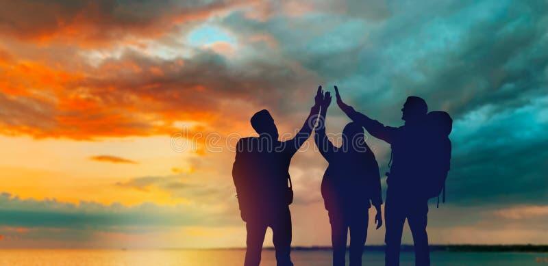 Ταξιδιώτες που κάνουν υψηλά πέντε πέρα από το ηλιοβασίλεμα διανυσματική απεικόνιση