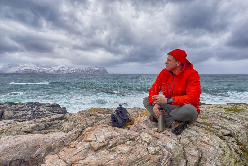 Ταξιδιώτης ατόμων στη ζωηρή πορτοκαλιά συνεδρίαση σακακιών στο βουνό και το τσάι κατανάλωσης Ενάντια στο βρυχηθμό των ωκεάνιων κα στοκ εικόνα με δικαίωμα ελεύθερης χρήσης