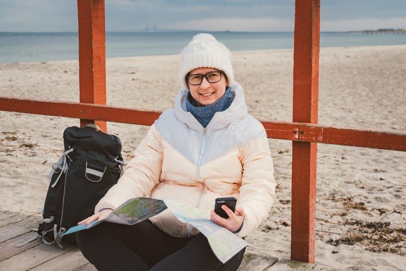 Ταξιδιώτης γυναικών με ένα σακίδιο πλάτης, έναν χάρτη και ένα τηλέφωνο Ταξίδι και ναυσιπλοΐα θέματος στην Ευρώπη Κορίτσι στο καπέ στοκ εικόνα με δικαίωμα ελεύθερης χρήσης