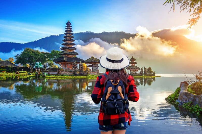 Ταξιδιώτης γυναικών με το σακίδιο πλάτης που κοιτάζει στο bratan ναό danu pura ulun στο Μπαλί, Ινδονησία στοκ φωτογραφίες