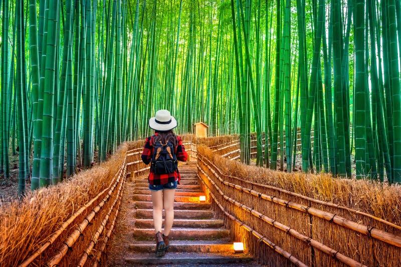 Ταξιδιώτης γυναικών με το σακίδιο πλάτης που περπατά στο δάσος μπαμπού στο Κιότο, Ιαπωνία στοκ φωτογραφία με δικαίωμα ελεύθερης χρήσης