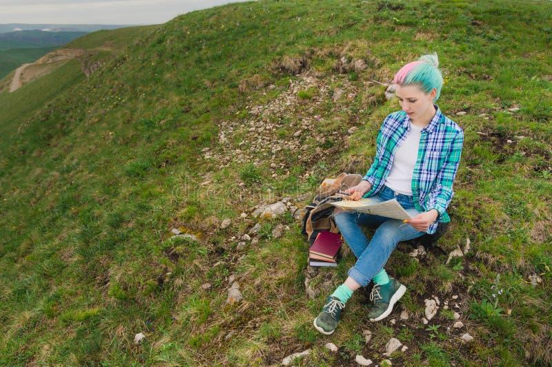 Ταξιδιώτης κοριτσιών με την πολύχρωμη συνεδρίαση τρίχας στην κάρτα ανάγνωσης φύσης και την εκμετάλλευση μια πυξίδα υπό εξέταση Η  στοκ εικόνες με δικαίωμα ελεύθερης χρήσης