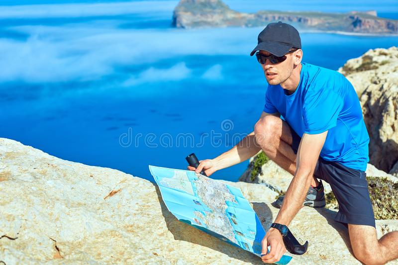 Ταξιδιώτης με το χάρτη και τηλεσκόπιο στον απότομο βράχο στοκ φωτογραφία