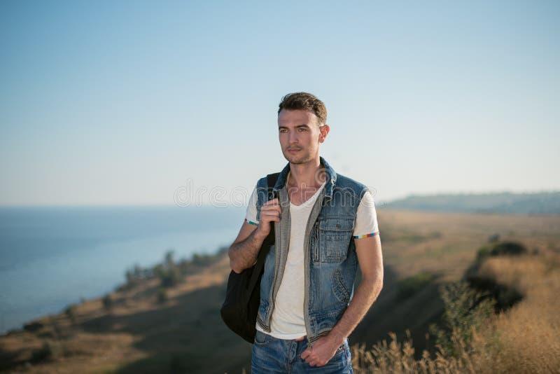 Ταξιδιώτης νεαρών άνδρων με τη χαλάρωση σακιδίων πλάτης υπαίθρια Θερινές διακοπές και πεζοπορία στοκ εικόνα με δικαίωμα ελεύθερης χρήσης
