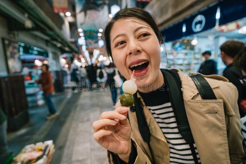 Ταξιδιώτης που δοκιμάζει χαρωπά τα ιαπωνικά τρόφιμα οδών στοκ εικόνα
